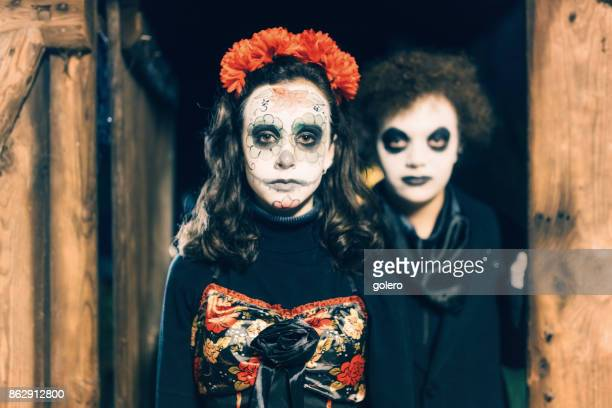 teenage girl and boy in spooky halloween costumes in old barn