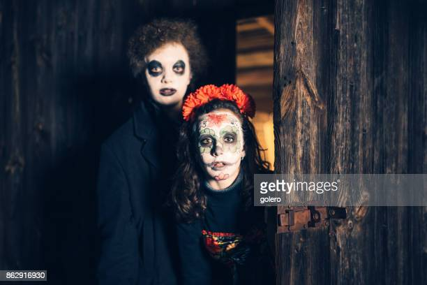 teenage girl and boy in spooky halloween masks in front of barn