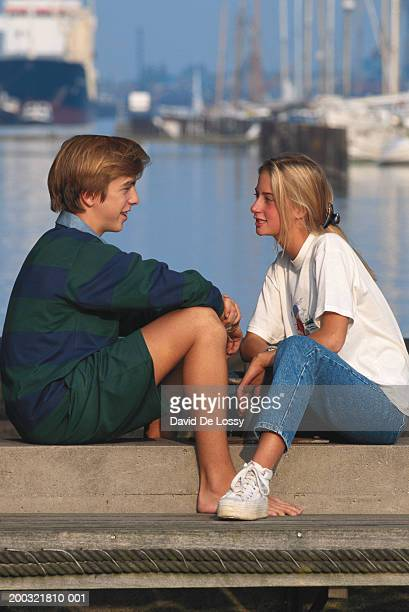 Teenage girl and boy (16-17) sitting face to face by harbour