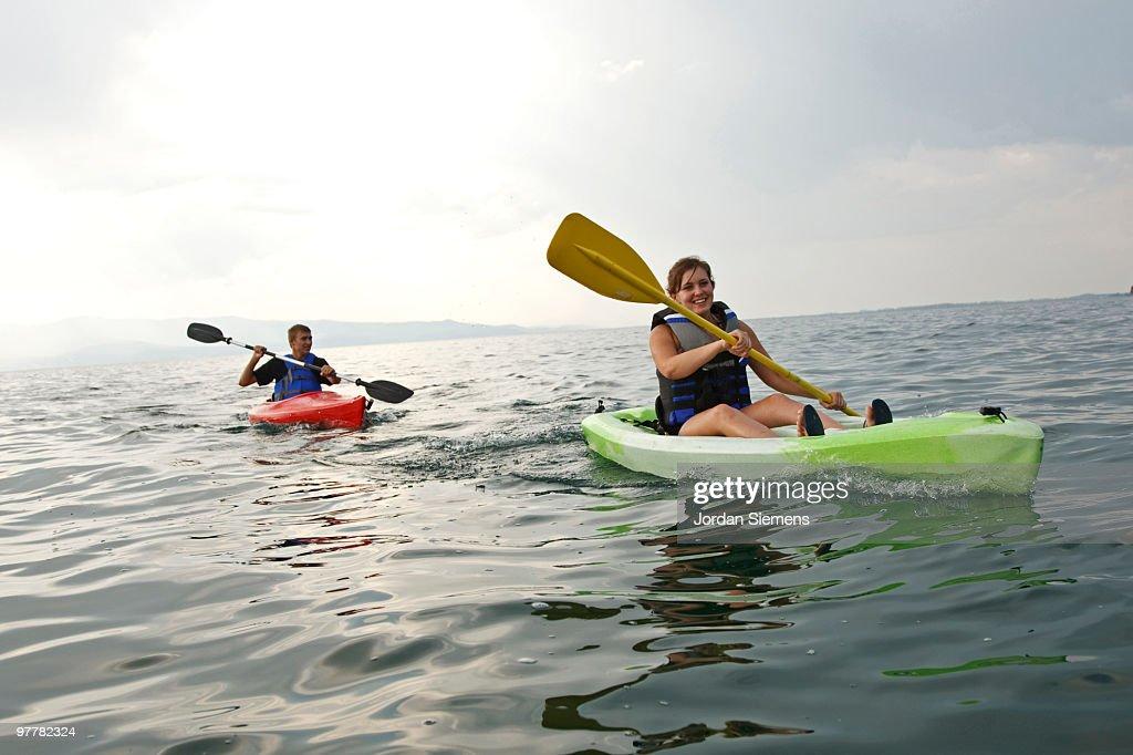 A teenage girl and boy smile as they paddle their colorful kayaks across Flathead Lake, Montana.