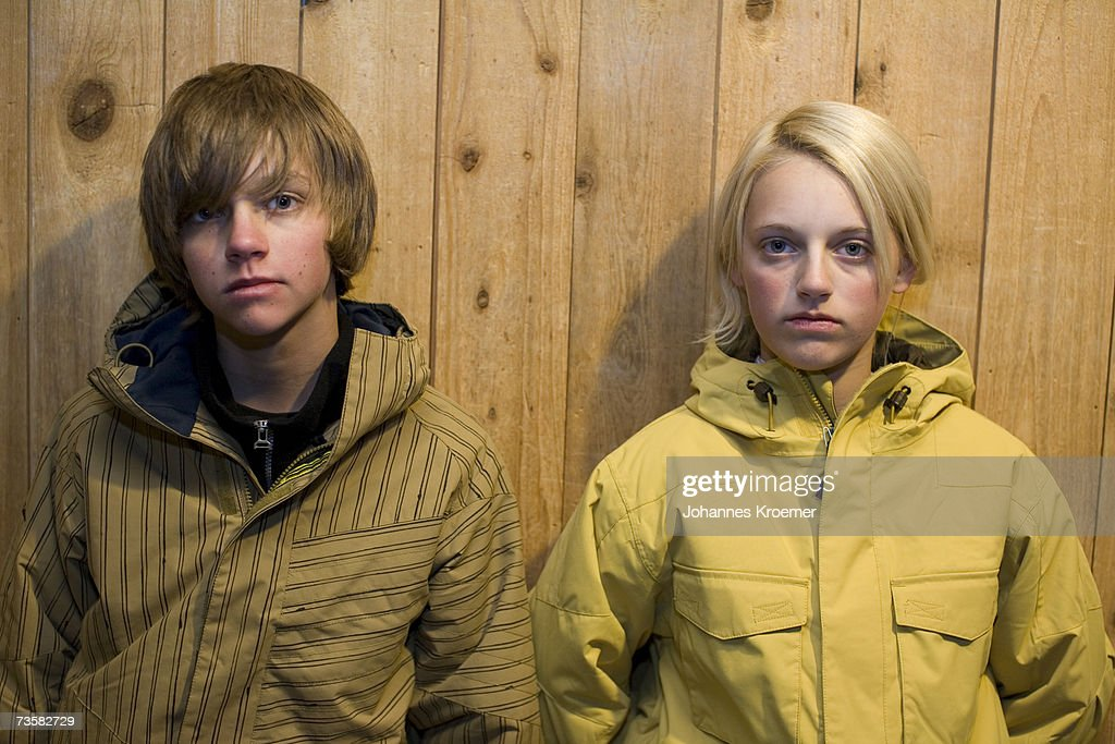 Teenage girl and boy (13-16) wearing ski jackets, standing side by side, portrait : Stock Photo