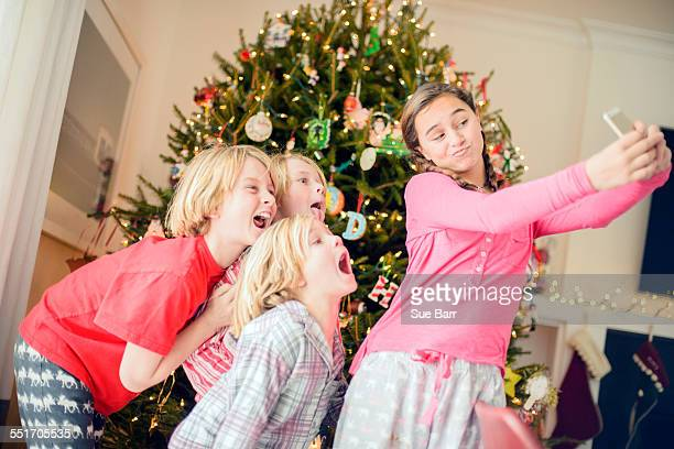 Teenage girl and brothers taking smartphone selfie at christmas