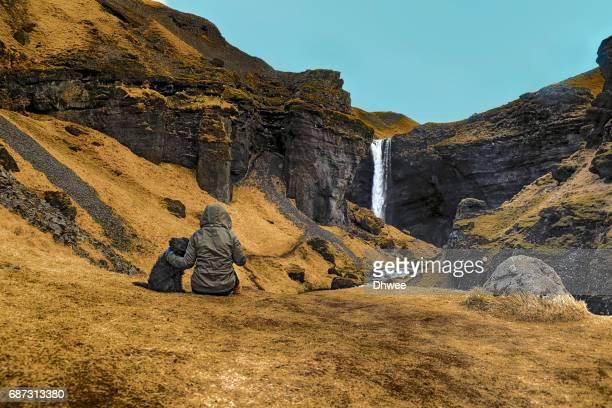 A Teenage Girl And Dog Sitting Enjoying Kvernufoss Waterfall, South Of Iceland