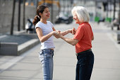 Teenage girl (14-16) and grandmother holding hands on pavement