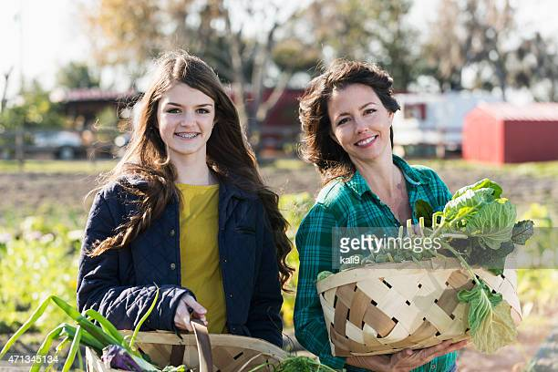 Teenage girl and mother with baskets of vegetables