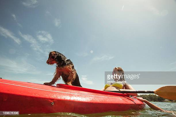 Teenage girl and pet dog in kayak