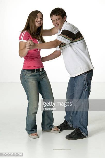 Teenage girl (16-17) and teenage boy (16-17) dancing together in studio