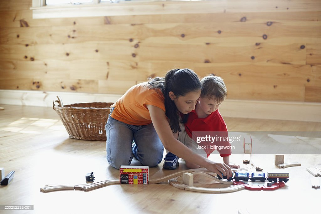 Teenage girl and young boy playing with a toy train
