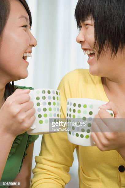 Teenage girl (16-17) and young woman holding coffee mugs, laughing