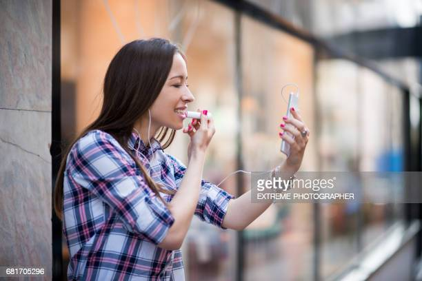 Teenage girl applying lip balm