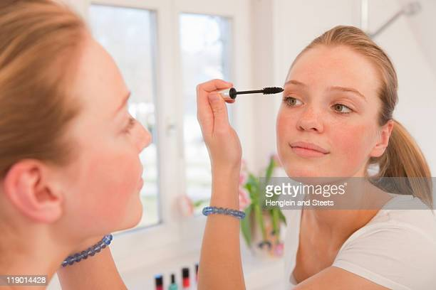 Teenage girl applying mascara