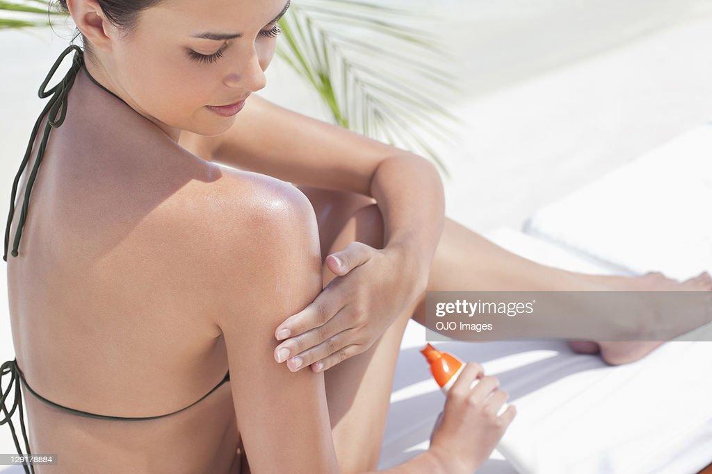 Teenage girl applying suntan lotion : Stock Photo