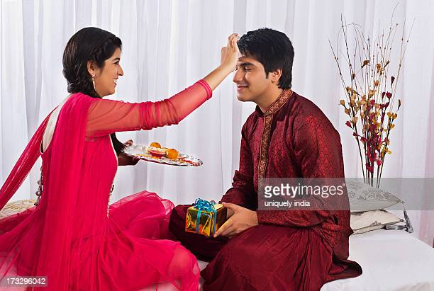 Teenage girl applying tilak to her brother at Raksha Bandhan