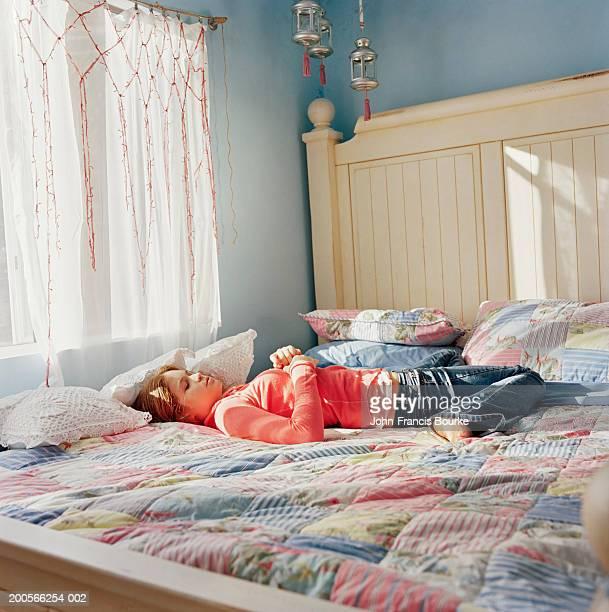 Teenage girl (14-15) asleep on bed