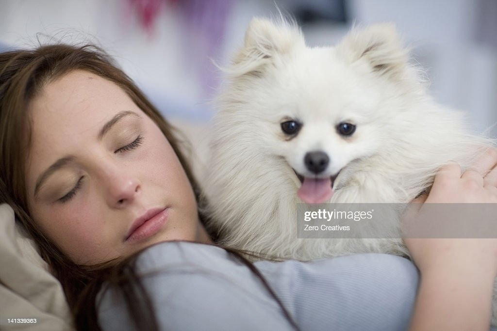 Teenage girl asleep with dog : Stock Photo