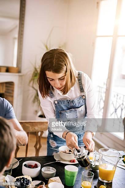 teenage girl at breakfast table serving coffee