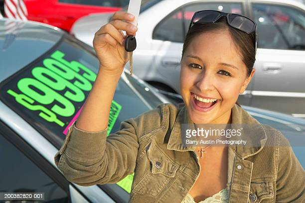 Teenage girl (17-19) at car lot, holding keys, smiling, portrait