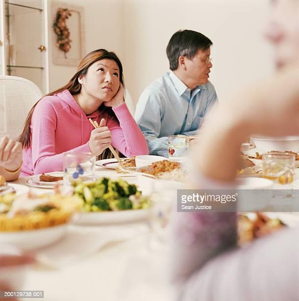 Teenage girl (16-18) at family dinner looking upward