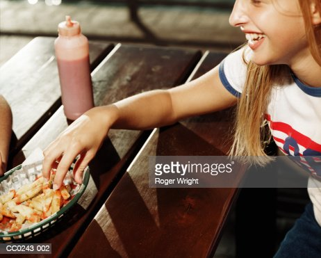 Teenage girl (13-15) at table, reaching for basket of chips : Stock Photo