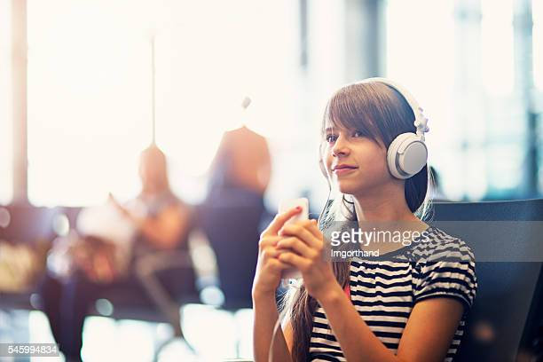 Teenage girl at the airport listening to music
