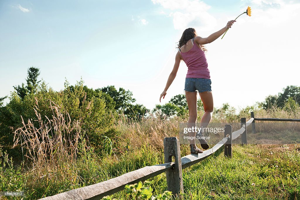 Teenage girl balancing on wooden fence : Stock Photo