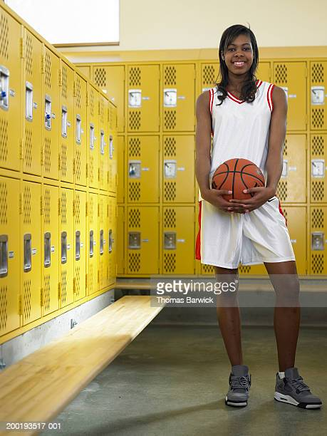 Teenage girl (15-17) basketball player holding ball, portrait