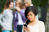 Teenage Girl Being Bullied By Text Message On Mobile Phone With Bullies In Background