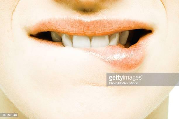 'Teenage girl biting lip, extreme close-up'