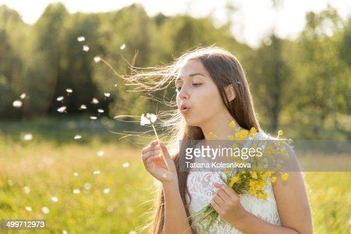 Teenage girl blowing dandelion