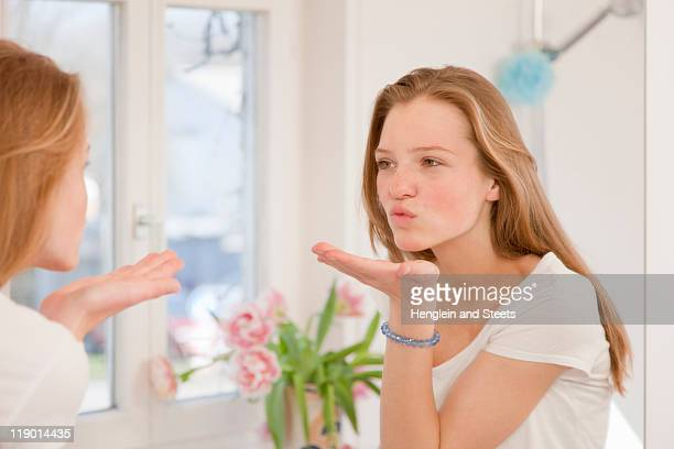 Teenage girl blowing kiss in mirror