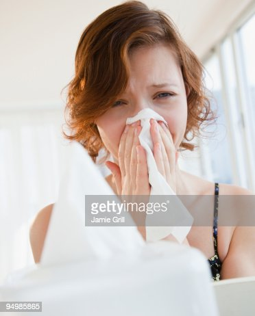 Teenage girl blowing nose with tissue : Stock Photo