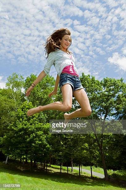 Teenage girl bouncing high in the air in the countryside