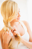 Teenage girl (16-17) braiding hair