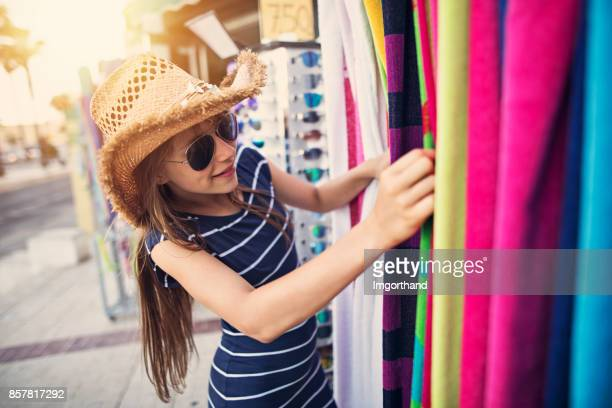 Teenage girl browsing beach towels on street market in Andalusia, Spain