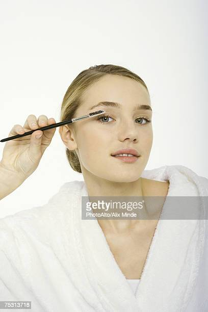 Teenage girl brushing eyelashes