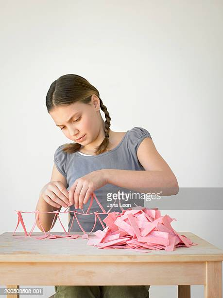 Teenage girl (11-13) building structure with pink bubblegum