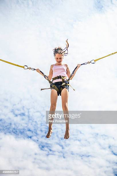 Teenage girl bungee jumping at trampoline