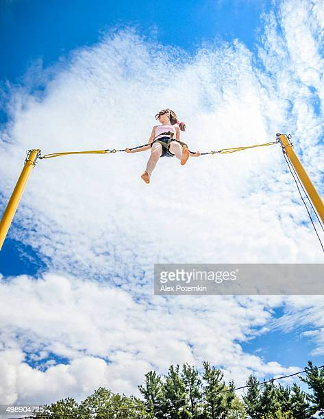 A teenage girl bungee jumping in the sky