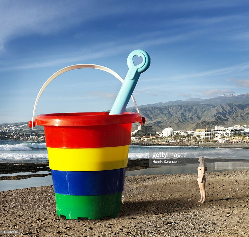 teenage by an oversize beach bucket and spade stock photo
