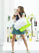 Teenage girl (17-19) carrying dog and shopping bags