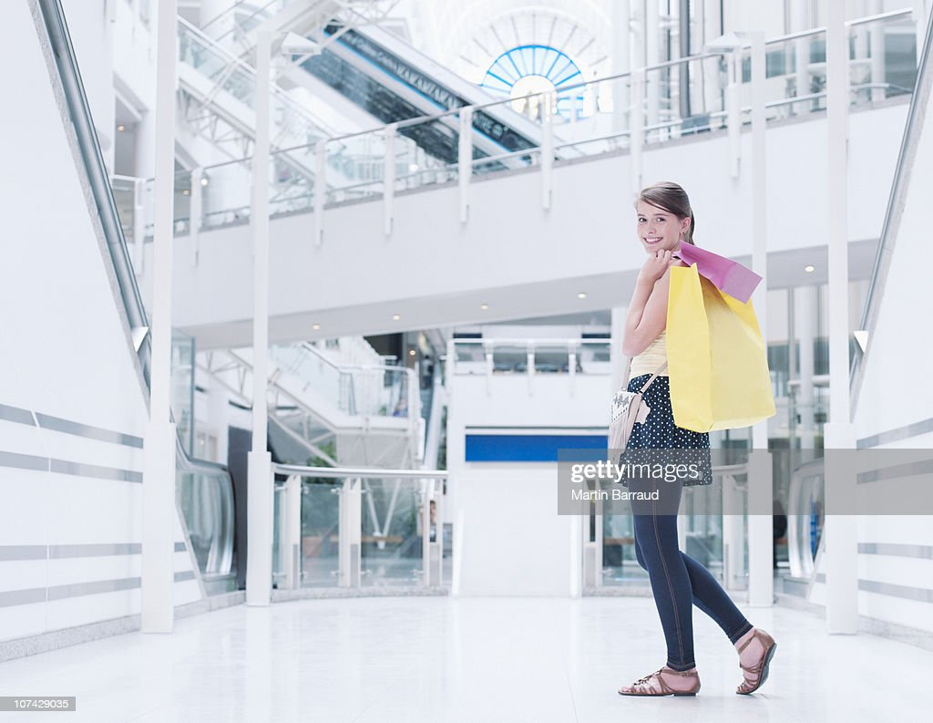 Teenage girl carrying shopping bags in mall : Stock Photo