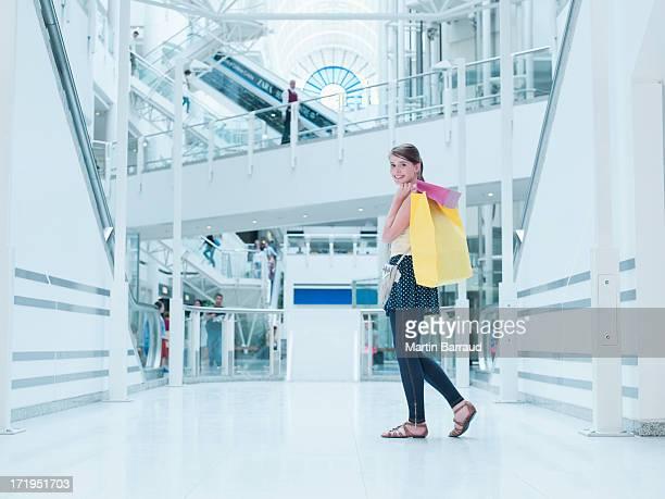 Teenager Mädchen tragen Einkaufstüten in Einkaufszentrum