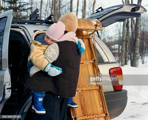 Teenage girl (13-15) carrying sleeping daughter (2-4) to car, winter