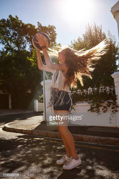 Teenage girl catching ball in street, Cape Town, South Africa