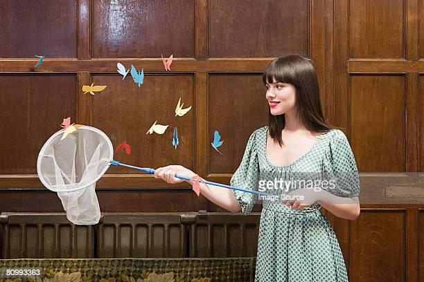 Une jeune fille avec un filet à papillons regardant