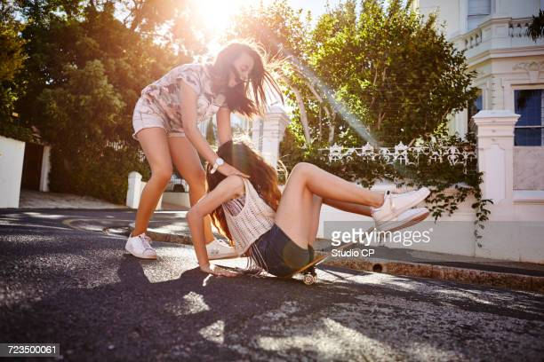Teenage girl catching friend falling off skateboard, Cape Town, South Africa
