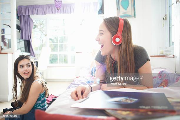 Teenage girl chatting to friend whilst listening to headphones in bedroom