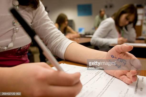 Teenage girl (15-17) cheating on math test (focus on formula on hand)