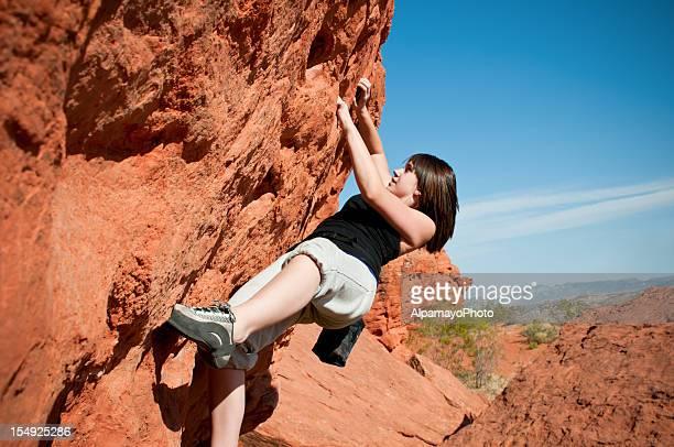 Teenage girl climbing boulder in Utah