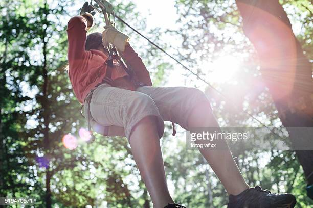 teenage girl climbs a Adventure Park in a forest